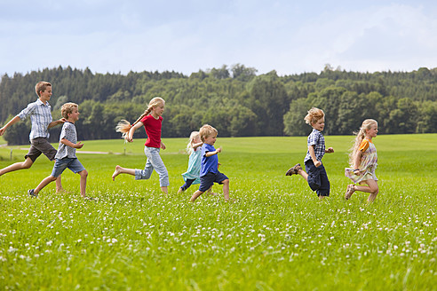 Germany, Bavaria, Group of children running through meadow - HSIYF000140