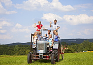 Germany, Bavaria, Woman with group of children sitting in old tractor - HSIYF000143