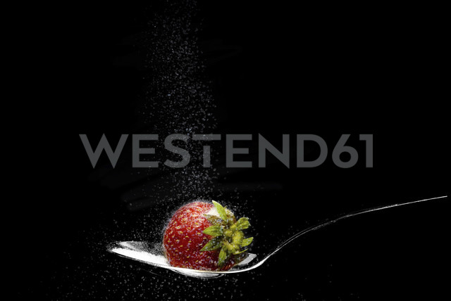 Strawberry on spoon with sprinkled sugar against black background - FDF000005