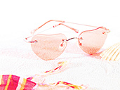 Heart shape sunglasses on sand, close up - FMKF000668