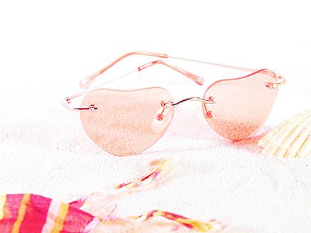 Heart shape sunglasses on sand, close up - FMKF000668