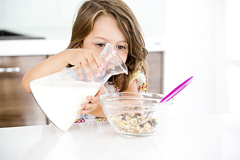 Germany, Girl pouring milk in muesli - RFF000025