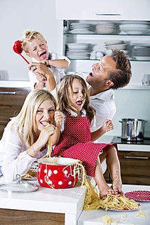 Germany, Family playing with spaghetti on kitchen worktop - RFF000064