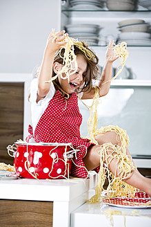 Germany, Girl playing with spaghetti on kitchen worktop - RFF000067