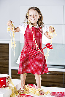 Germany, Girl playing with spaghetti on kitchen worktop - RFF000070