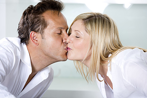 Germany, Mid adult couple eating noodles and kissing - RFF000079