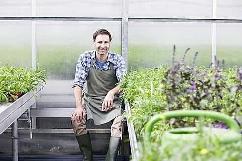 Germany, Bavaria, Munich, Mature man in greenhouse between rocket plant - RREF000016