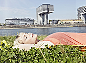Germany, Cologne, Young woman relaxing in grass - RHYF000205