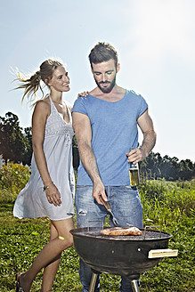 Germany, Cologne, Young couple grilling sausage and drinking beer - RHYF000219
