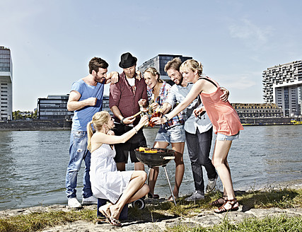 Germany, Cologne, Group of people gathered around barbecue - RHYF000261