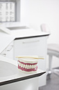Germany, Exhibition dentures with toothbrush in dental office - FMKYF000164