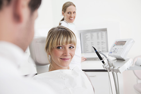Germany, Dentist and patient in clinic, smiling - FMKYF000197