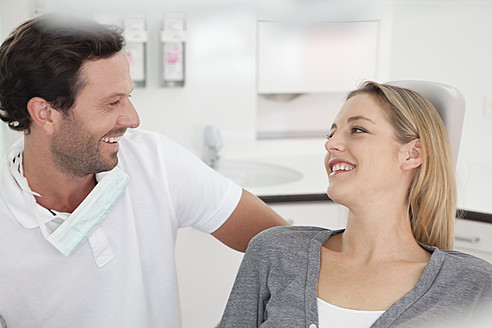 Germany, Dentist and patient in clinic, smiling - FMKYF000206