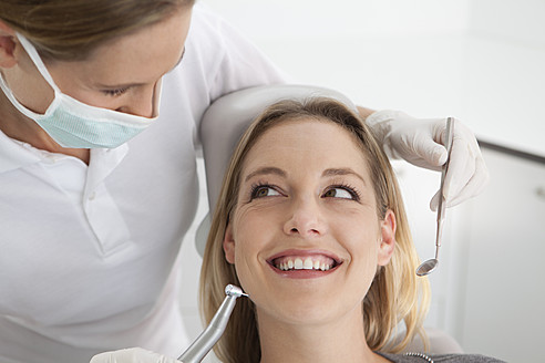Germany, Young woman getting her teeth examined by dentist - FMKYF000212