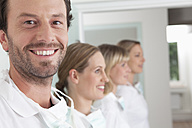 Germany, Dentist and assistance smiling - FMKYF000242