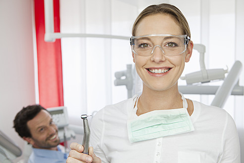 Germany, Dentist with safety glasses, patient in background - FMKYF000254