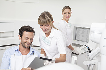 Germany, Dentist showing clipboard to patient - FMKYF000260