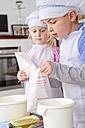 Germany, Girl and boy using baking powder - FKF000076