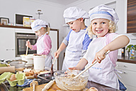 Germany, Girls and boy preparing dough and baking cup cake in kitchen - FKF000088