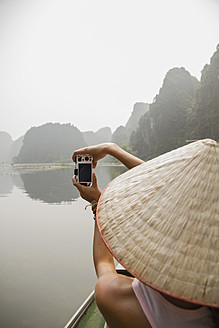 Vietnam, Ninh Binh, Young tourist taking photograph of landscape - MBEF000527