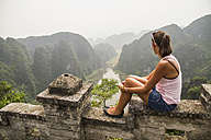 Vietnam, Ninh Binh, Young tourist looking down to Tom Coc valley - MBEF000530