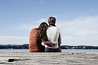 Germany, Bavaria, Couple sitting on jetty at Lake Starnberg - RBF001055