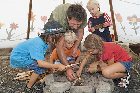 Germany, Munich, Father with children preparing camp fire in tent - TCF002996