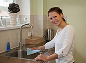 Germany, Brandenburg, Young woman cleaning kitchen sink, smiling, portrait - BFRF000111