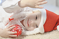 Boy holding christmas bauble, smiling, portrait - MJF000156
