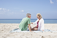 Spain, Mallorca, Senior couple sitting at beach - PDYF000206