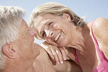 Spain, Mallorca, Happy senior couple sitting at beach - PDYF000276