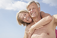 Spain, Senior man giving piggy back ride to woman - PDYF000270