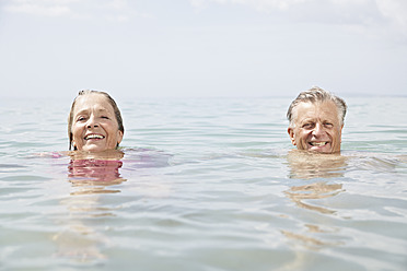 Spain, Senior couple swimming in sea - PDYF000243