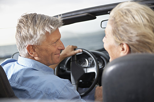 Spain, Senior couple looking at each other in convertible car - PDYF000234