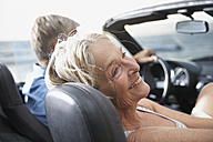 Spain, Senior couple in convertible car, smiling - PDYF000231