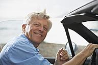 Spain, Senior man in convertible car, smiling, portrait - PDYF000228