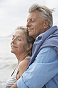 Spain, Senior couple on beach at Atlantic, smiling - PDYF000222