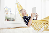 Germany, Bavaria, Munich, Woman relaxing in hammock and watching digital tablet - RBYF000222