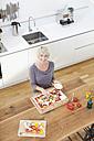 Germany, Bavaria, Munich, Woman preparing pizza in kitchen - RBYF000239