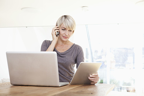 Germany, Bavaria, Munich, Woman working with digital tablet and talking on phone - RBYF000328