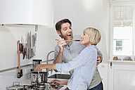 Germany, Bavaria, Munich, Mature woman cooking food while man feeding - RBYF000262