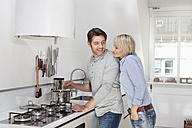 Germany, Bavaria, Munich, Mature couple preparing food in kitchen - RBYF000264