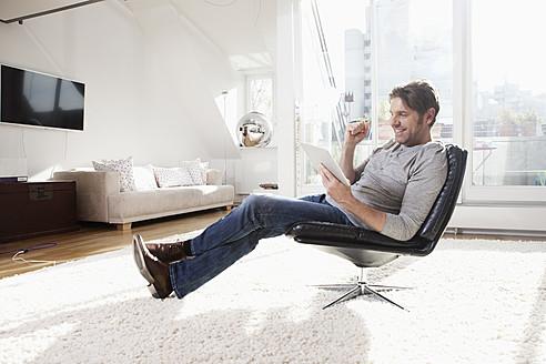 Germany, Bavaria, Munich, Man using digital tablet, smiling - RBYF000287