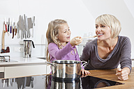 Germany, Bavaria, Munich, Daughter feeding mother in kitchen, smiling - RBYF000304