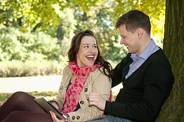 Germany, Berlin, Couple sitting in autumn park with digital tablet, smiling - BFRF000120