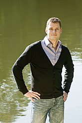 Germany, Berlin, Mid adult man standing at lake, smiling, portrait - BFRF000126