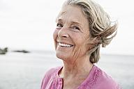 Spain, Senior woman smiling at Atlantic ocean - WESTF019049