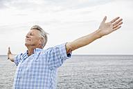 Spain, Senior man stretching on beach - WESTF019055