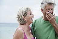 Spain, Senior couple smiling on beach - WESTF019091