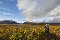 USA, Alaska, Tourist taking photograph of Alaska Range in autumn - FOF004414